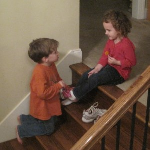 Joshua helps Addy with her shoes.